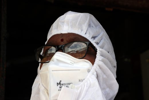 A health worker takes a moment after screening people  for COVID-19 at Dharavi slum in Mumbai, India, Wednesday, June 24, 2020. India is the fourth hardest-hit country by the pandemic in the world after the U.S., Russia and Brazil.