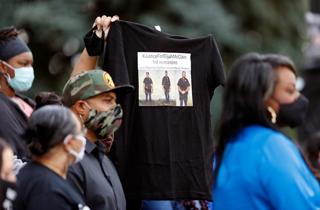 A supporter holds up a shirt to call attention to the death of Elijah McClain in August 2019 in Aurora, Colo., during a news conference on the west steps of the State Capitol after Colorado Governor Jared Polis signed a broad police accountability bill Friday, June 19, 2020, in downtown Denver.
