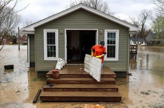 Robin Morrow carries out a flood-damaged door at her home in Utica, IN, on March 1, 2018. Marrows says they'll have to gut the inside but glad the flood wasn't as high as in 1997, where the roof was covered.