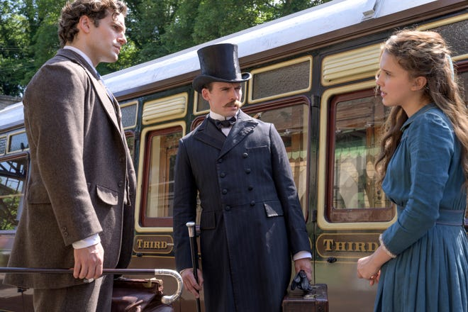 "Enola (Millie Bobby Brown) reconnects with older brothers Sherlock (Henry Cavill, left) and Mycroft (Sam Claflin) in ""Enola Holmes."""