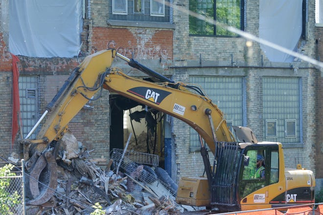 A contractor removes items from the former Banta Corp. printing plant at the corner of Ahnaip and Racine streets in Menasha.