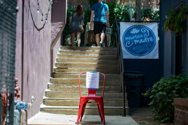 A sign announcing the requirement of masks is taped to a chair outside of Mountain Madre in downtown Asheville on June 25, 2020. Governor Cooper announced that face masks will be required state-wide indoors and outdoors where social distancing is not possible starting June 26.