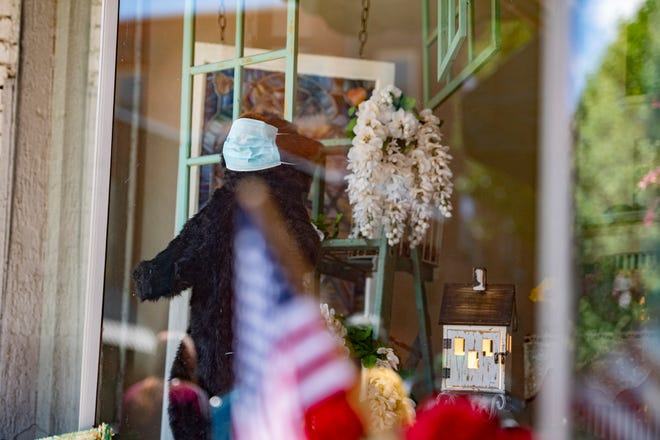 A bear wears a mask in the window of The Cottage in downtown Asheville on June 25, 2020. Governor Cooper announced that face masks will be required state-wide indoors and outdoors where social distancing is not possible starting June 26.