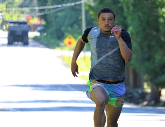 South Kitsap graduate Deyondre Davis sprints uphill on the road in front of his home in Port Orchard. Davis is headed to the University of Idaho on a track and field scholarship.