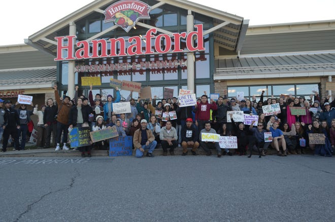 Activists with the Milk with Dignity campaign hold signs outside of a Hannaford supermarket in Middlebury.