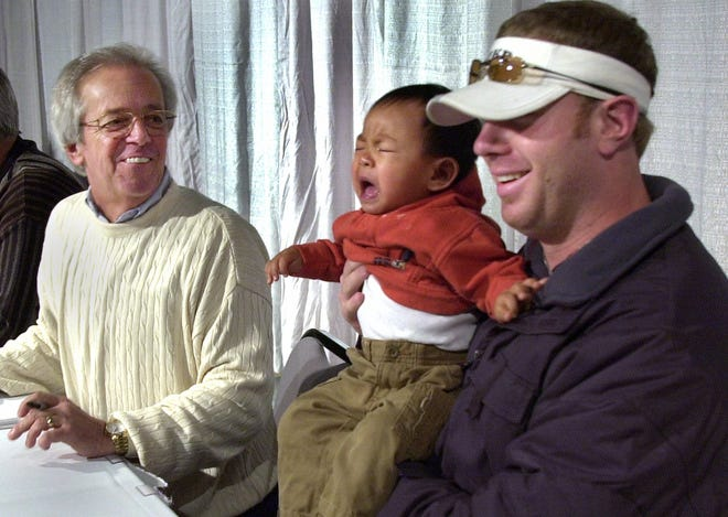 JANUARY 25, 2002: Adam Dunn holds Ethan Daniels, 15 months, of Lima, Ohio while they pose for a photo for Ethan's parents, although the boy was a little cranky. Marty Brennaman smiles next to them at a stop in Lima, Ohio, as a small group of the Cincinnati Reds headed out on a tour bus for a three state trip.