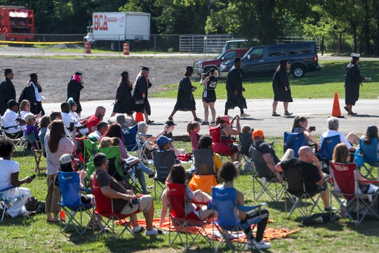 Parents sit in lawn and camping chairs to watch before their graduating seniors line up and walk to receive their diplomas during Operation Graduation, an outdoor ceremony for Clarksville area students at Clarksville Speedway & Fairgrounds in Clarksville, Tenn., on Wednesday, June 24, 2020.