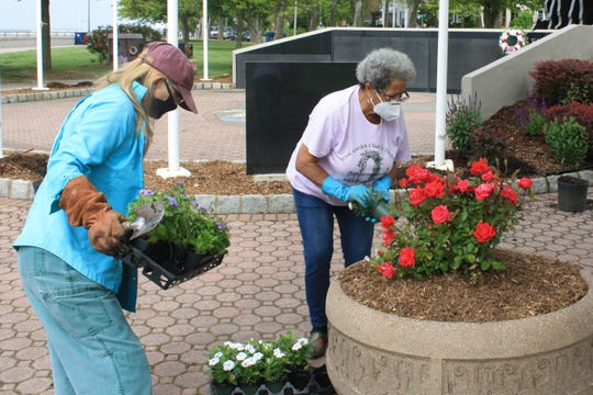 Royal Garden Club members Donna Pemberton and Betty Crews plant flowers at Perth Amboy's Veterans' Memorial.