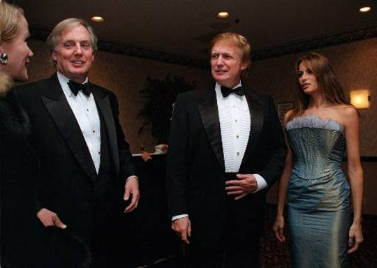In this Nov. 3, 1999, file photo, real estate developer Donald Trump, center right, with his date Melania Knauss, right, speaks to his sister-in-law Blaine Trump, left, as his brother Robert Trump listens at a dinner in New York.