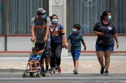 Visitors wearing masks to protect against the spread of COVID-19 walk through downtown San Antonio, Wednesday, June 24, 2020. Cases of COVID-19 have spiked in Texas and the governor of Texas is encouraging people to wear masks in public and stay home if possible.