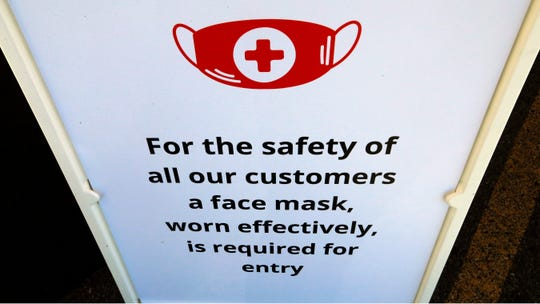 "In this Tuesday, June 23, 2020, photo, a ""Face Covering"" sign is shown at Snider Bros. Meats, in Holladay, Utah."