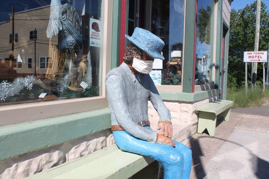 A masked mannequin sits outside the door of Nonesuch Crafts and Guitar shop in Ontonagon, Michigan, Thursday.