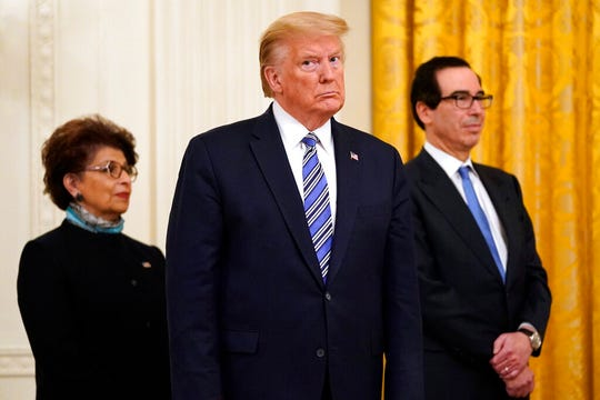 In this April 28, 2020 file photo President Donald Trump, along with Jovita Carranza, administrator of the Small Business Administration, and Treasury Secretary Steven Mnuchin listen during an event about the Paycheck Protection Program used to support small businesses during the coronavirus outbreak.