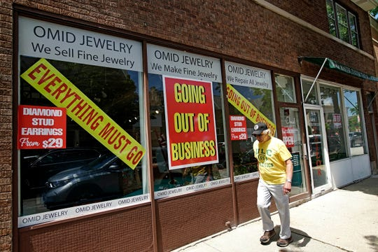 A man walks past a retail store that is going out of business due to the coronavirus pandemic in Winnetka, Ill., Tuesday.