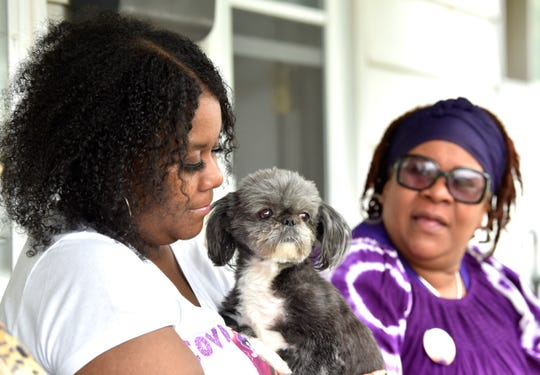 COVID-19 survivor Johtasha Mosley, left, and sister Dilanda Mosley sit on the porch with Johtasha's shih tzu Basil.