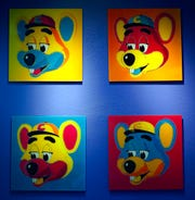 This Jan. 16, 2014 file photo shows paintings hanging  on a wall at Chuck E. Cheese's in Dallas. Chuck E. Cheese pizzeria, that Mecca of fun for children but the bane of many parents, is filing for bankruptcy protection.