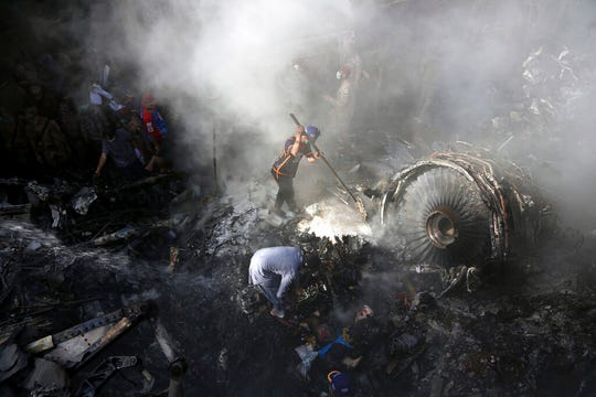 In this May 22, 2020 file photo, volunteers look for survivors of a Pakistan International Airlines plane that crashed in a residential area of Karachi, Pakistan. Pakistan's state-run airline announced Thursday, June 25, 2020, it will ground 150 pilots on charges they obtained their pilot licenses by having others take exams for them.