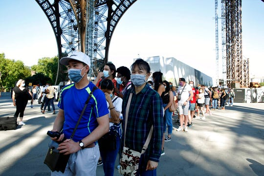 People queue up prior to visit the Eiffel Tower, in Paris, Thursday, June 25, 2020.