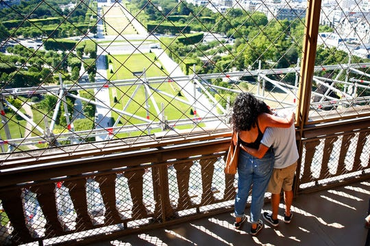 A couple hugs each other as they visit the Eiffel Tower, in Paris, Thursday, June 25, 2020.