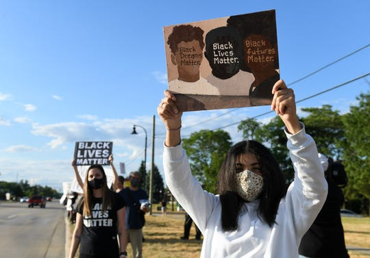 Kiarra Coger of Shelby Township holds a sign she painted as people protest against racism on Van Dyke Road near the municipal buildings on Wednesday.