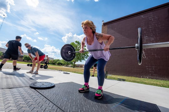 Brenda Kerscher of Madison Heights lifts weights during an outdoors cross-fit class at High Caliber Strength and Fitness, in Troy, June 25, 2020.