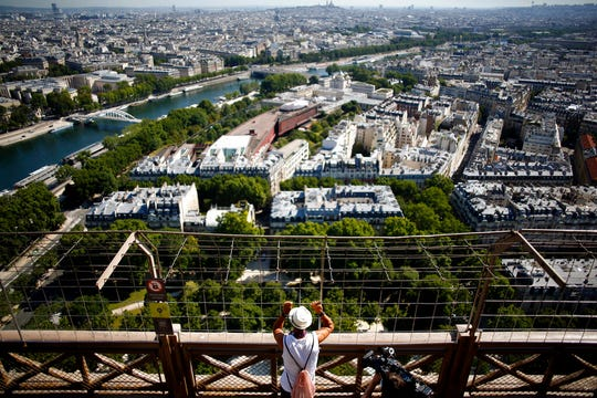 A visitor looks at the view from the Eiffel Tower, in Paris, Thursday, June 25, 2020. The Eiffel Tower reopens after the coronavirus pandemic led to the iconic Paris landmark's longest closure since World War II.