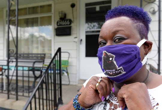 Lokesia Mosley of Detroit shows off the mask she wears in honor of her sister, Johtasha Mosley, who is home now in Eastpointe after being in the hospital for almost 94 days due to COVID-19.