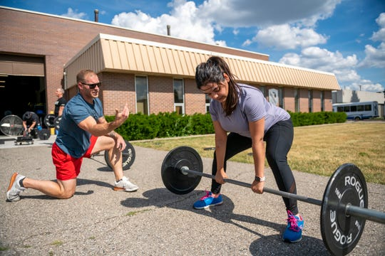 Travis Heidt, head coach and owner of High Caliber Strength and Fitness in Troy, guides Apoo Rambhatla, of Rochester Hills, during an outdoors cross-fit class, June 25, 2020.