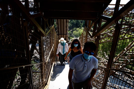 People climb stairs as they visit the Eiffel Tower, in Paris, Thursday, June 25, 2020. The Eiffel Tower reopens after the coronavirus pandemic led to the iconic Paris landmark's longest closure since World War II.
