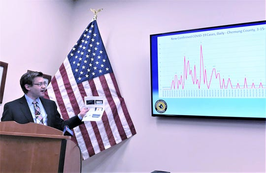 Chemung County Public Health Director Peter Buzzetti shows a graph explaining how the county's coronavirus number have remained stable over the past few months during a Thursday news conference.