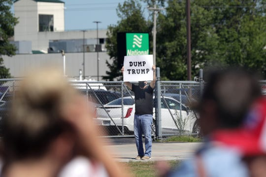 A lone protester holds a sign as people stand in line to attend a President Donald Trump's town hall meeting on Thursday at the Jet Air Group facility at Green Bay Austin Straubel International Airport in Ashwaubenon.