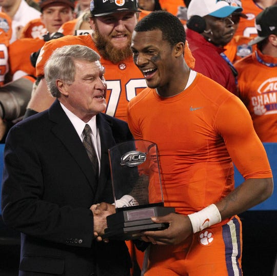 John Swofford (left), ACC Commissioner, awards Clemson quarterback Deshaun Watson the MVP Trophy after the ACC Championship game in Charlotte, North Carolina.  The Tigers ran out the clock after the play and won 45-37.