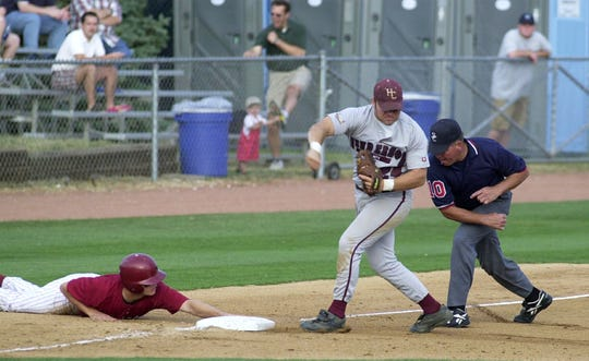 Henderson County's Neil Sellers, center, reacts as third base umpire Steve Hawkins, right, calls out Ballard runner Mike Jarboe during a double play between first and third bases during the 2000 state championship game at Cliff Hagan Stadium in Lexington.