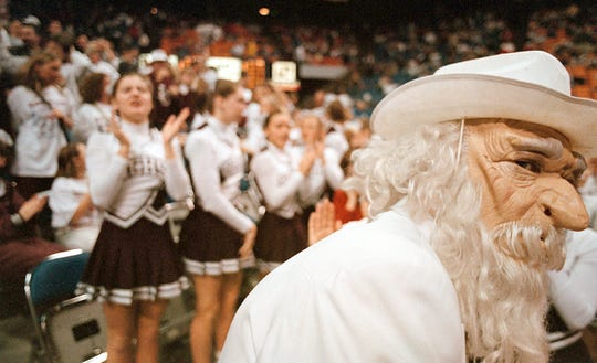 As the HCHS cheerleaders warm up in the background, the Colonel mascot looks for the team as they exit the court before the 1999 Sweet 16 semifinal game against Ballard.