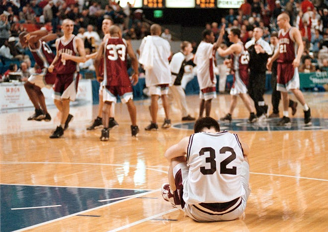Henderson County's Brandon Fisher reflects on the game as Ballard team members and fans celebrate their victory over the Colonels in the 1999 Sweet 16 semifinal game.