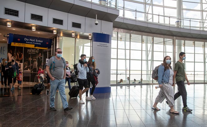 Travelers, most with masks, head away from their arriving gates at the Indianapolis International Airport, Indianapolis, Wednesday, June 25, 2020. Mask use varies on different airlines, and some, like Allegiant, have a more lax policy than others.