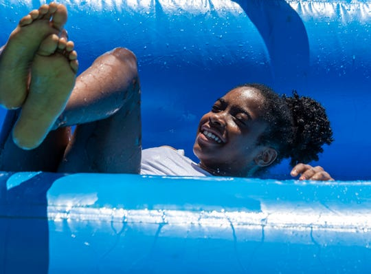 Amora Atwater, 11, slides down the waterslide at the Keep my Hood Good event. This event brought families and friends together for summer fun activities with a water slide, arts & crafts and a chance to talk about stories from the bible at Jackson, Tenn., Thursday, June 25, 2020.