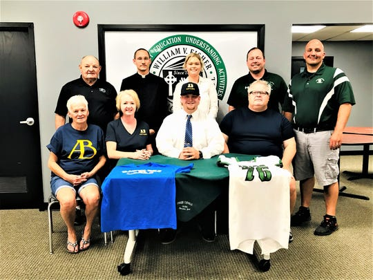 Fisher Catholic's Christian Gaul recently signed to play college football at Alderson Broaddus. He earned All-Ohio honors twice and helped lead the Irish to back-to-back playoff appearances. Seated with  Gaul is his grandmother, Sue Mora and his parents, Bethany and David Gaul. Standing left to right: Fisher Catholic assistant coach John Young, Father Ty Tomson, Gaul's sister, Meredith, Fisher Catholic principal Jim Globokar and Fisher Catholic head football coach Luke Thimmes.