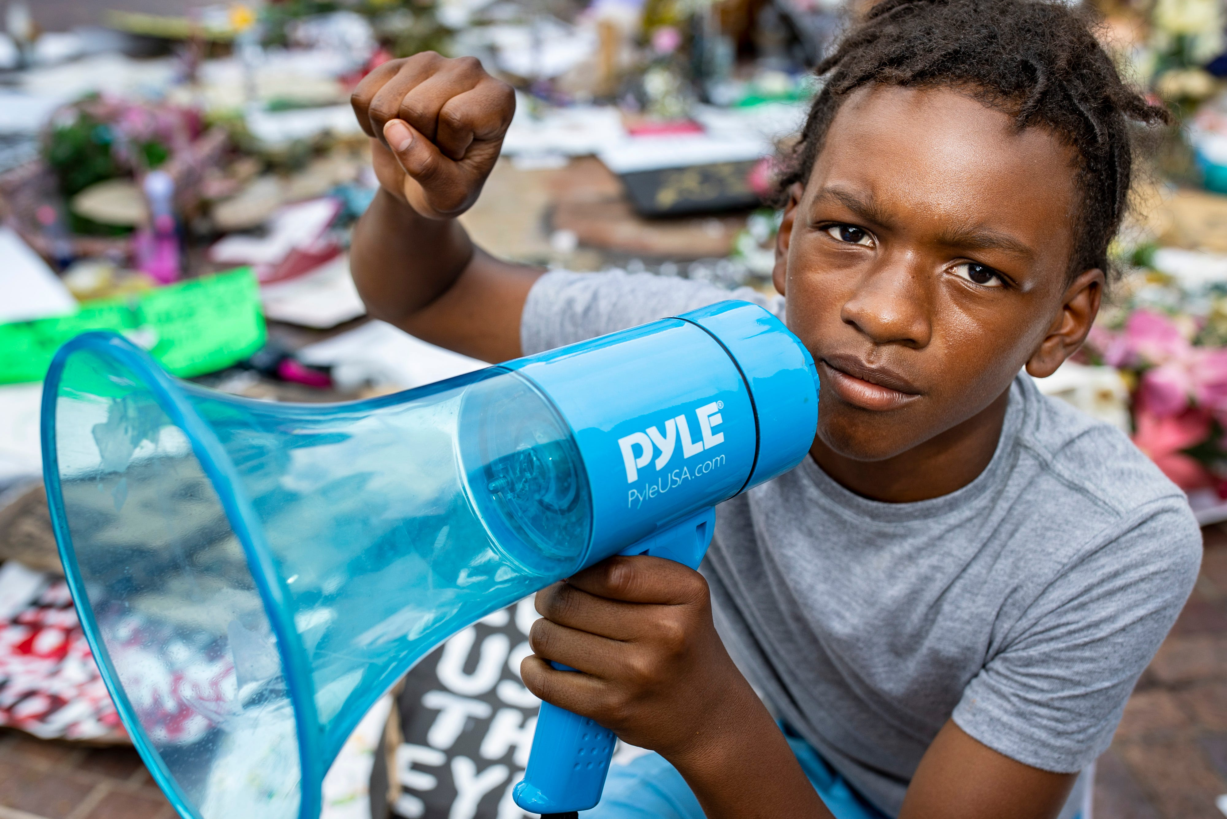 """Keshawn Johnson, 12, kneels while raising a fist at the Breonna Taylor mural in Jefferson Square Park in Louisville, Ky. Johnson has often led chants during protest marches. """"I feel like this is what I need to do for everyone to get justice,"""" Johnson says. """"I have little people that look up to me, and I don't want the generation after me to go through what I am."""""""