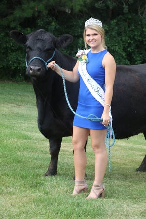 Mariah Richardson poses with a cow, crown and sash after being named Waukesha County's Fairest of the Fair 2021.
