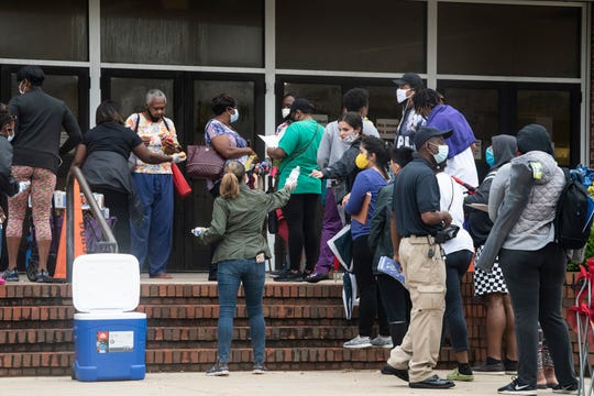 Volunteers hand out water and snack as people wait in line to troubleshoot unemployment claims outside the Dunn-Oliver Acadome in Montgomery, Ala., on Thursday, June 25, 2020.