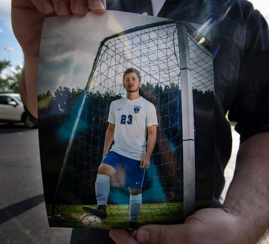 Ryan Gurley holds a picture of 16-year-old construction worker Gustavo Enrique Ramirez during a vigil for Ramirez Wednesday, June 24, 2020 in Nashville, Tenn. Ramirez died after falling 120 feet from a scaffold at a hotel construction site on Interstate Drive in Nashville.