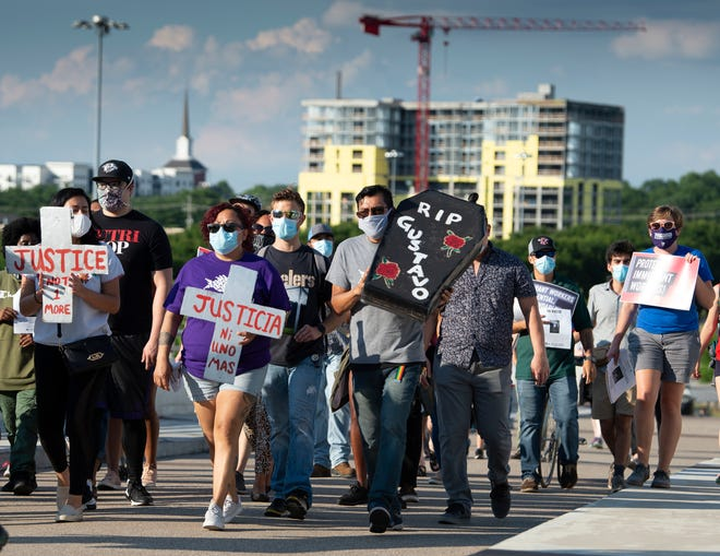 Protestors march across the pedestrian bridge to call attention to the death of 16-year-old construction worker Gustavo Enrique Ramirez Wednesday, June 24, 2020 in Nashville, Tenn. Ramirez died after falling 120 feet from a scaffold at a hotel construction site on Interstate Drive in Nashville.