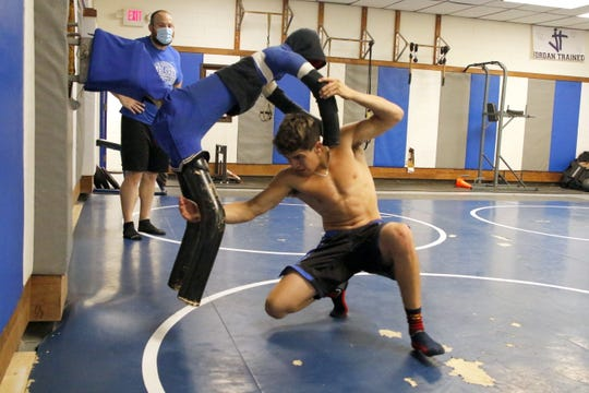 """Carlsbad junior Jesse Rodriguez works with """"Adam"""" while head coach Joe Bach watches his technique on June 25, 2020."""