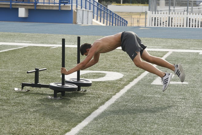 The Carlsbad football team works out on June 23, 2020. Half the team spends its session in the weight room while the other half is outside focusing on cardio.