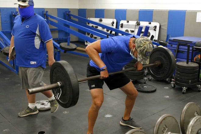 Carlsbad assistant coach Matt Enloe gets some lifting in with the football team on June 23, 2020.