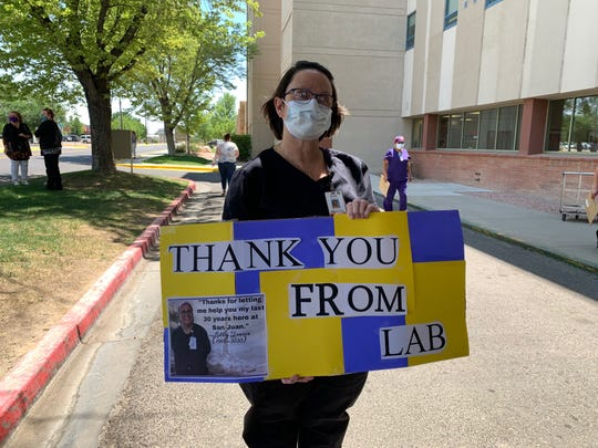 A San Juan Regional Medical Center employee holds a sign as staff welcomed an EMS escort of Lilly Tsosie on June 19 when her body was transported from Albuquerque.