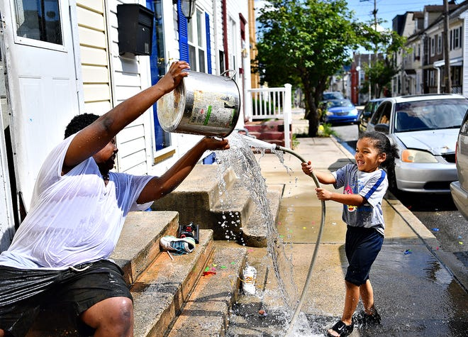 Jaheim Stokes, 12, left, and Jai'kai Andrews, 4, enjoy a water fight on South Hartley Street as temperatures reach around 82 degrees in York City, Wednesday, June 24, 2020. Dawn J. Sagert photo