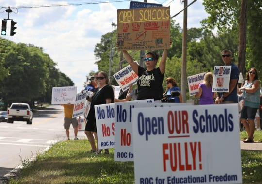 Wendy Wilson joins with dozens of others in holding up signs for passing motorists to see at the ROC for Educational Freedom rally held outside the Penfield Central School District administration building on Atlantic Avenue Thursday, June 25, 2020. People at the rally were calling for officials to fully open public schools in September.