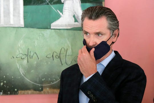 In this June 9, 2020 file photo Gov. Gavin Newsom wears a protective mask on his face while speaking to reporters at Miss Ollie's restaurant during the coronavirus outbreak in Oakland, Calif.